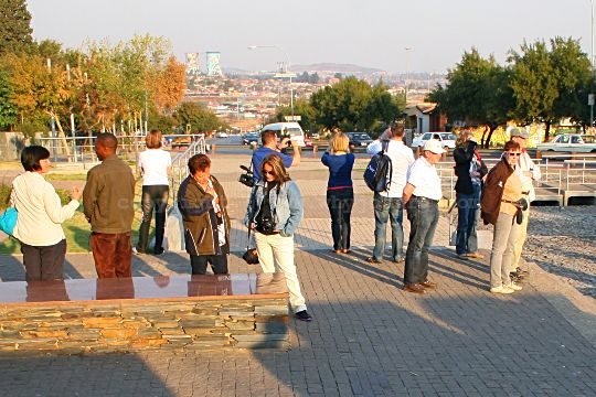 Tourists at the Hector Pieterson Memorial, listening to a site guide, look out over Soweto and the Orlando Towers in the distance.