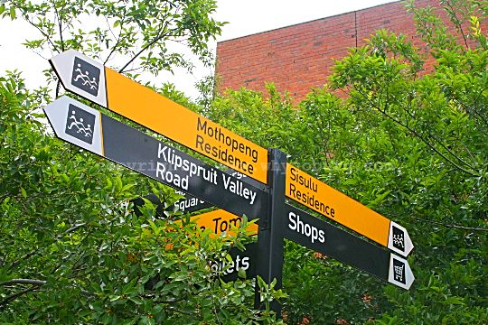 Multiple information signs fixed to a pole displaying various sites of interest in the vicinity of the Hector Pieterson Museum in Soweto