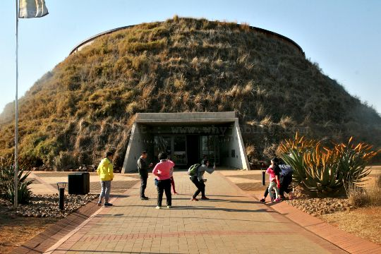 A family taking photos outside the Tumulus museum building at Maropeng